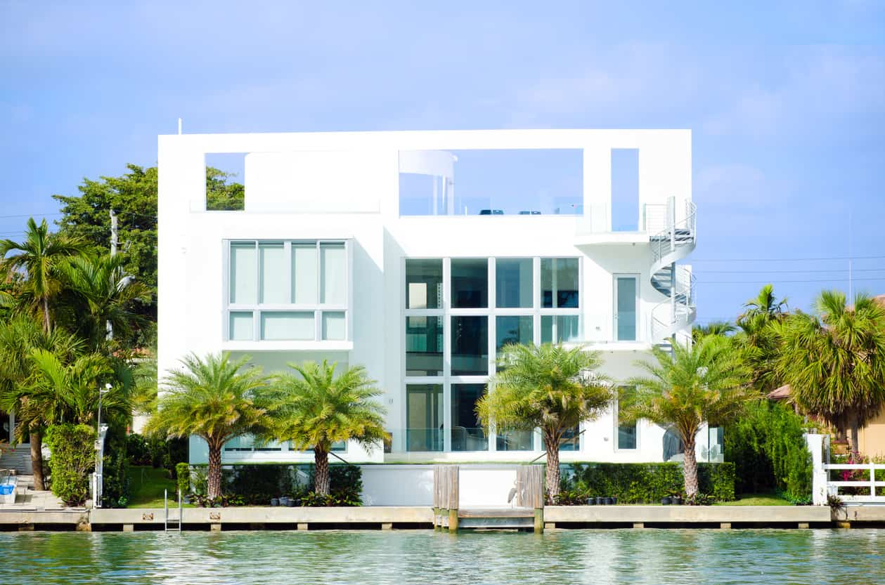 White Florida mansion on waterway with huge windows and rooftop patio