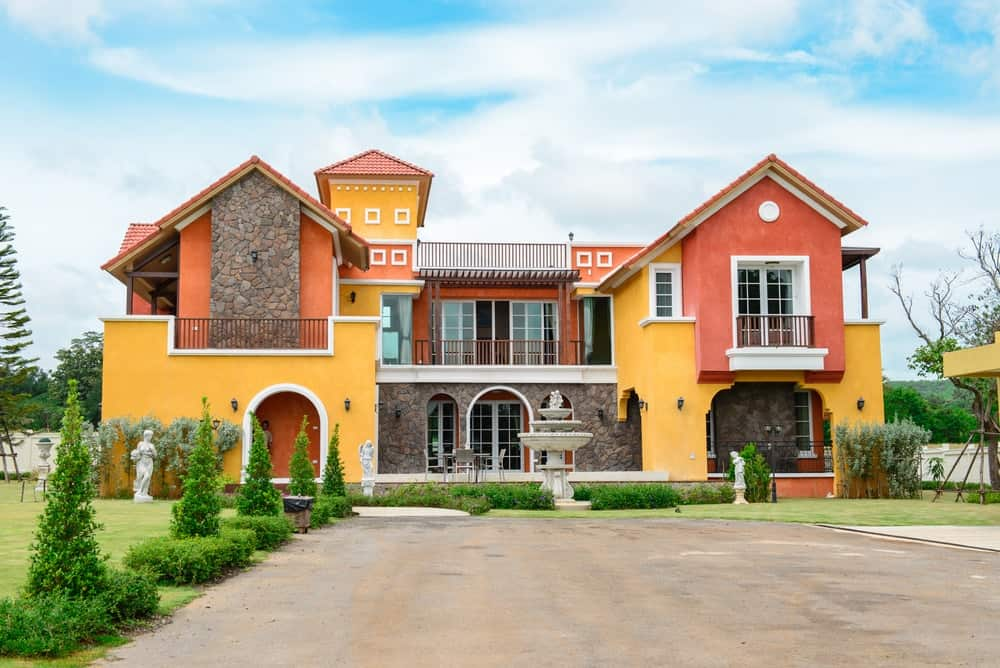 This Tuscan style luxury house will never go unnoticed with its interplay of vivid orange and yellow facade. Its warm tones offset the boldness of the colors while white trims are used to showcase geometric details.