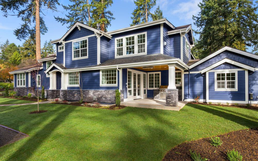 A blue exterior siding pair off with off white trims for a traditional look. The stone brick foundation perches the house with visual texture.