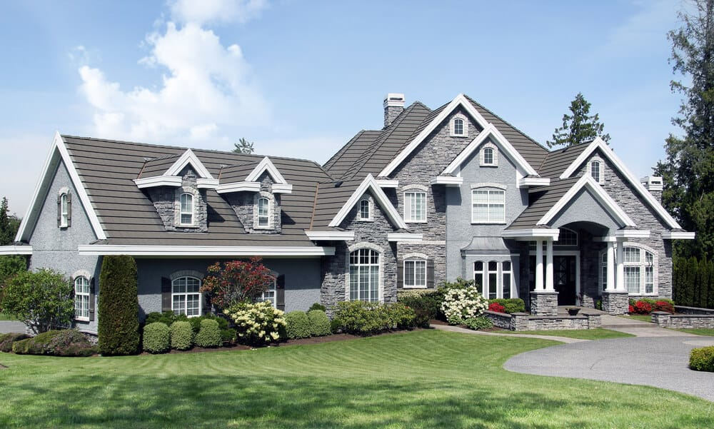 A gray-toned, stone house which is not that tall but definitely wide and spacious. Its roof and windows are accented with a white lining for a better emphasis.