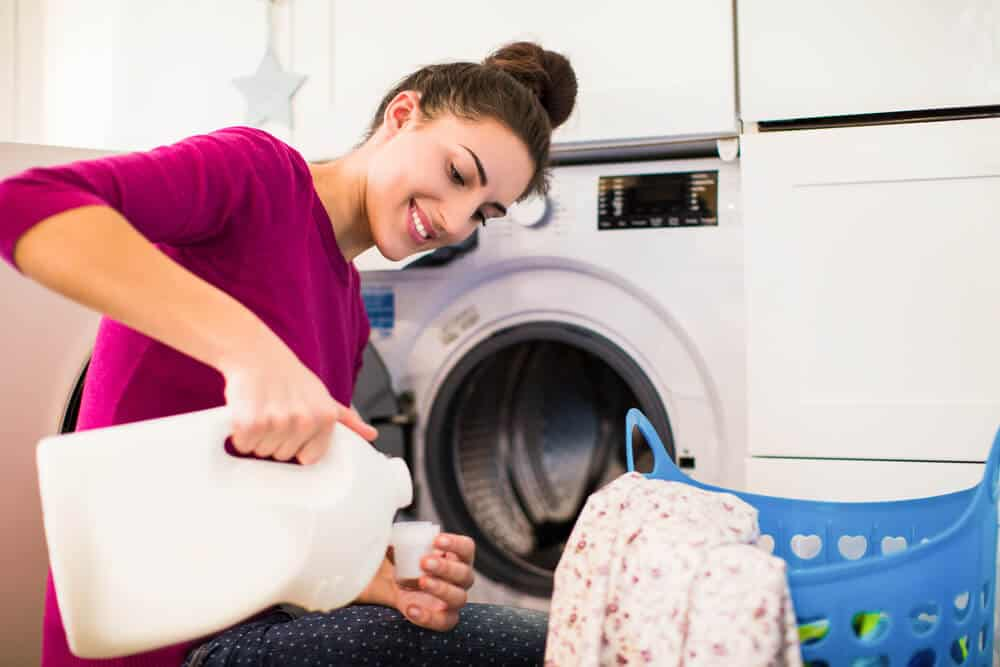 A woman in a high bun, doing her laundry.