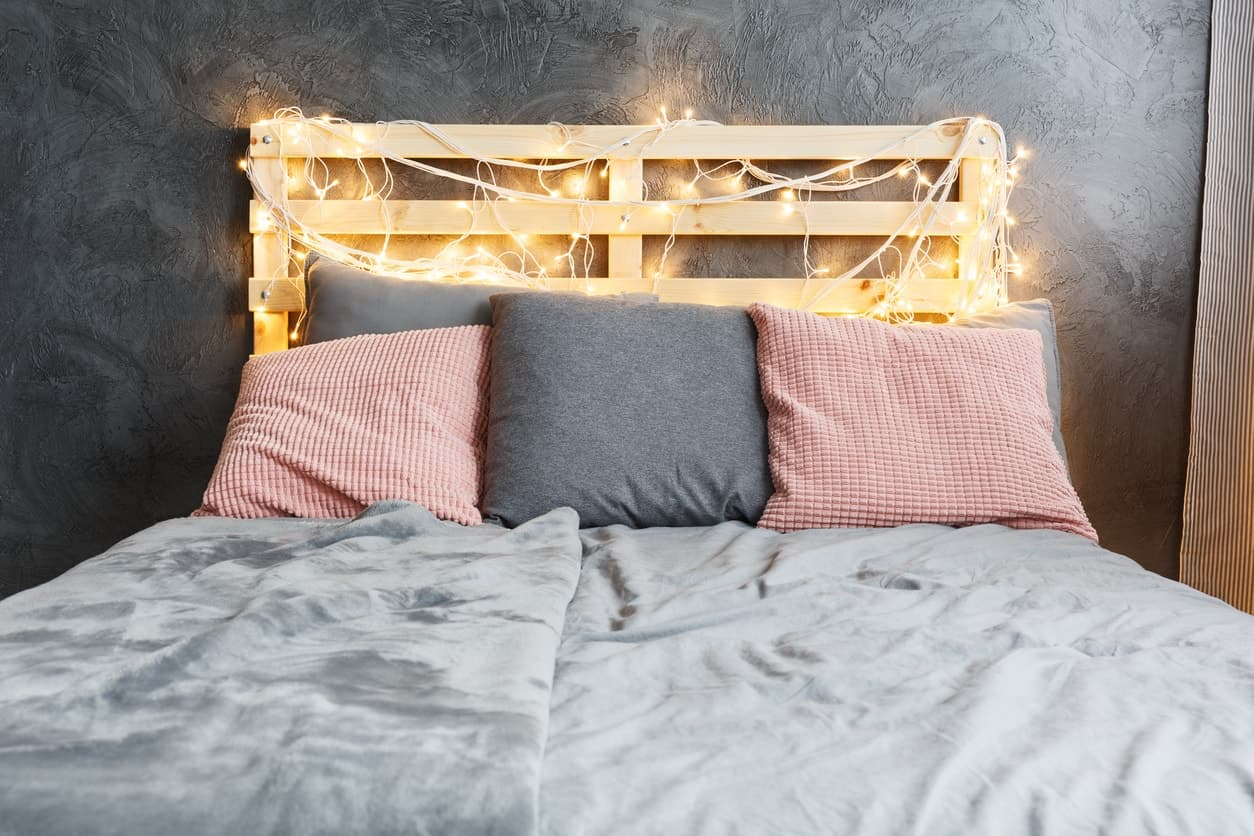 Wood pallet with string lights used as headboard with gray and red pillows, gray bedding and dark gray wall.