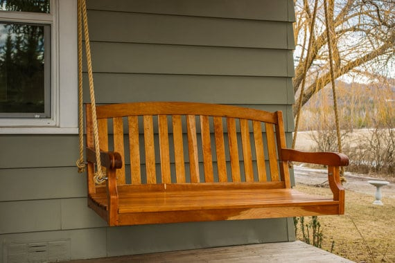 Wooden porch swing with a varnished finish.