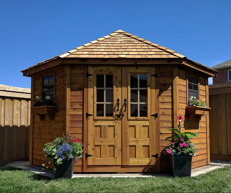 Beautifully designed wooden shed with flowers outside.