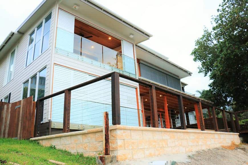 A large beach house with a wooden and glass exterior, along with a nice fence.