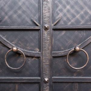 Wrought iron door with circular handles.