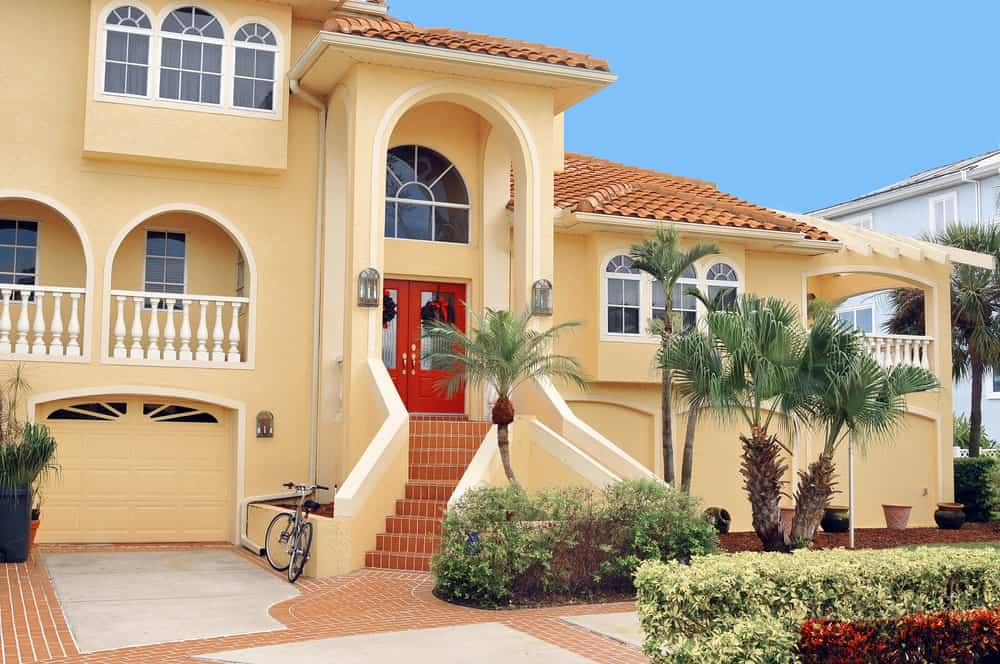 Yellow stucco house with brick driveway and an exterior staircase leading to the front door under a two-story arch.