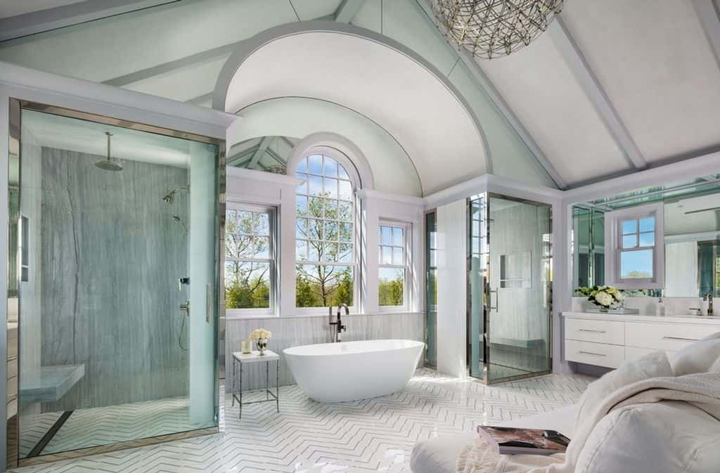 The master bathroom has two large walk-in showers flanking a freestanding tub in an alcove.  The color scheme is mint green, gray and white.