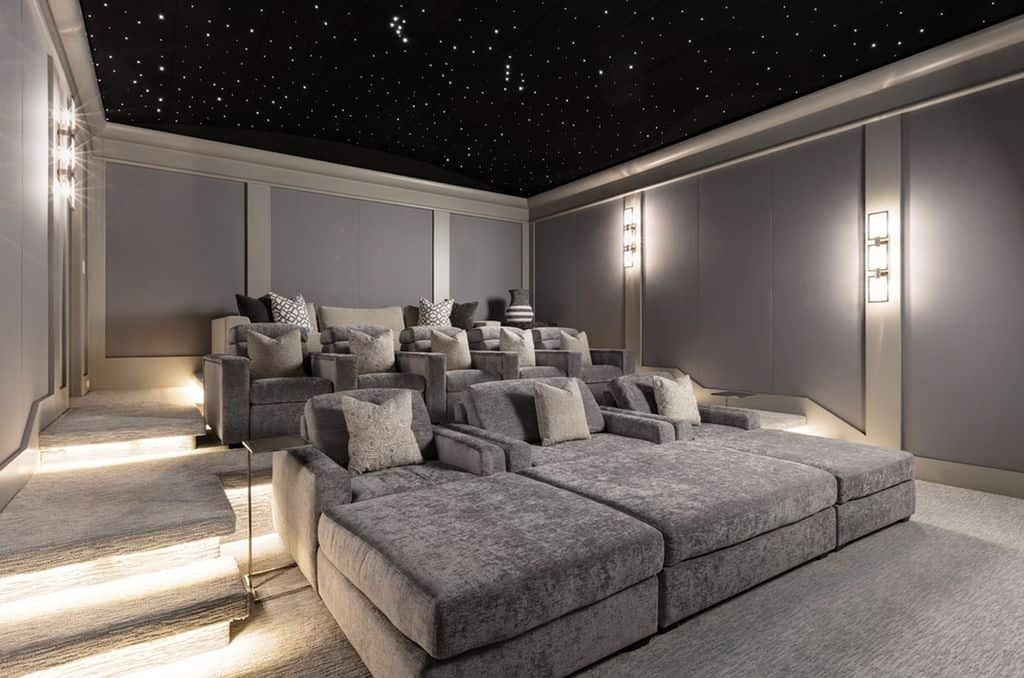 Large tiered home movie theater with ultra comfortable armchairs topped with a space-like ceiling.