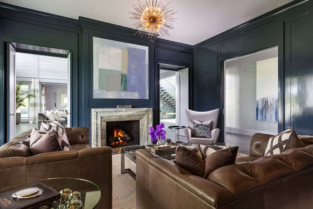 Masculine lounge room with fireplace.  Dark blue-gray walls work great with the overstuffed brown leather furniture.
