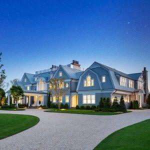 View of new Southampton mega mansion front drive at dusk