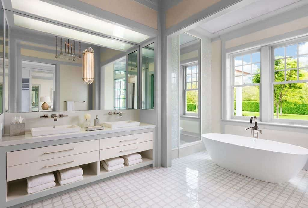 Spacious contemporary light gray and white bathroom with white freestanding tub looking out over the sprawling grounds.