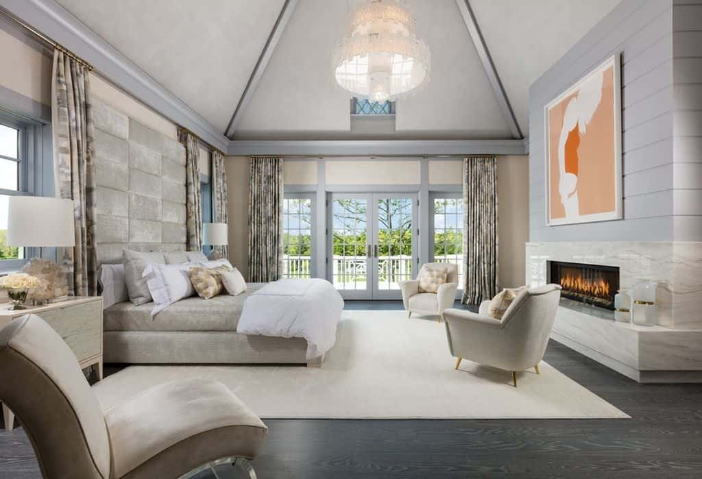 Sumptuous light gray and beige primary bedroom with multiple accent chairs, large gas fireplace, and private deck.  The light gray walls contrast nicely with the dark hardwood flooring.  The room is made that much nicer with soaring ceiling and white chandelier.