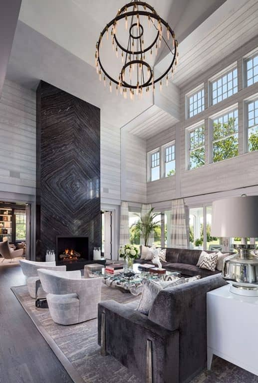 Large two-story formal living room with huge wrought iron chandelier and gorgeous custom grey and brown furniture.