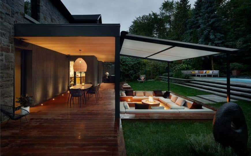 This is a view of the back of the house with stone exterior walls complemented by the wooden deck walkway that leads to a sunken conversation pit with a fire pit in the middle for warmth.