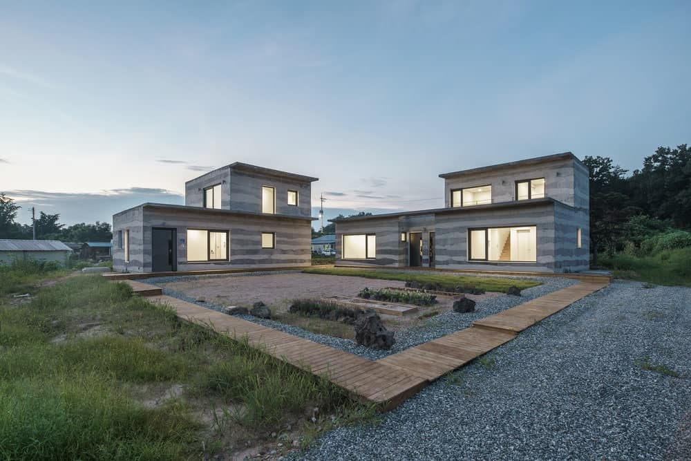 This is a view of the house with two stone structures that stand up due to the striped concrete design of the exterior walls complemented by the garden.