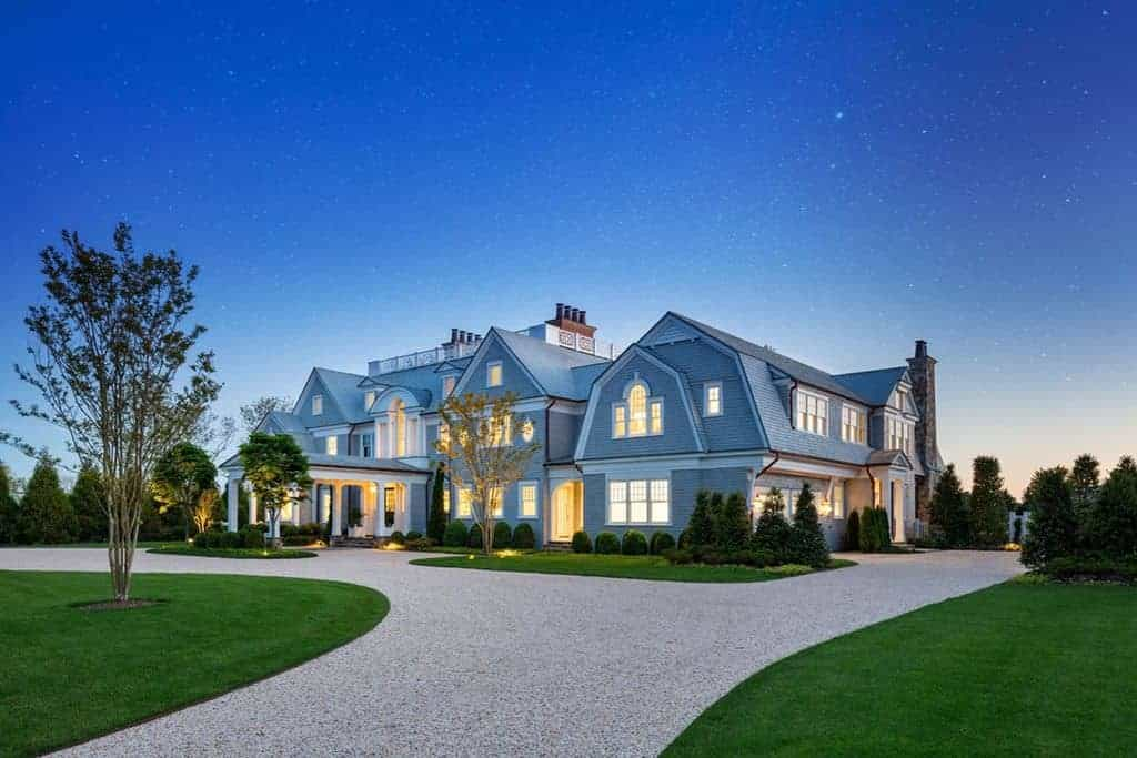 A 23,000 sq. ft. mega mansion with a gray exterior and a sprawling front and back yards.
