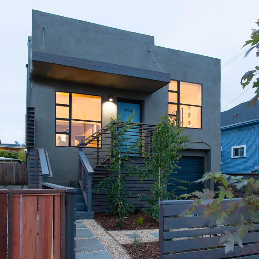 Modern home with a gray exterior. It features a small garden area with a nice walkway.