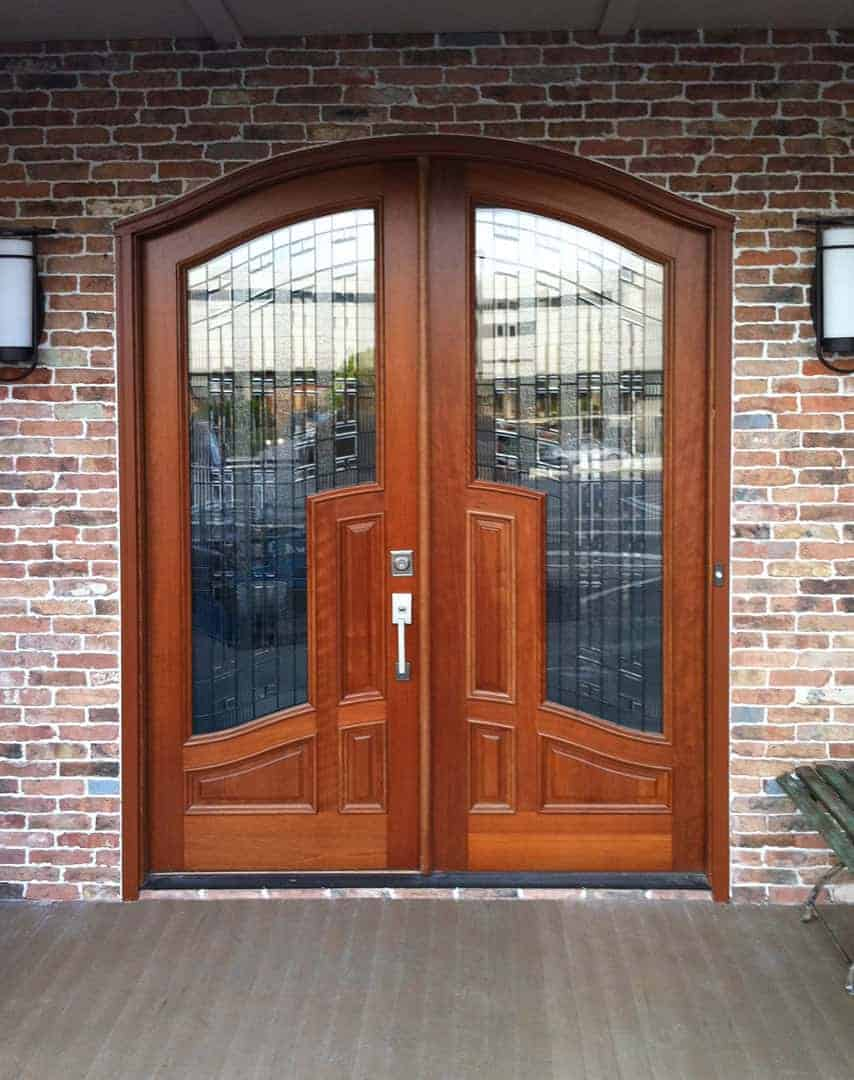 Arched mahogany double front door with large glass panels surrounded by brick exterior