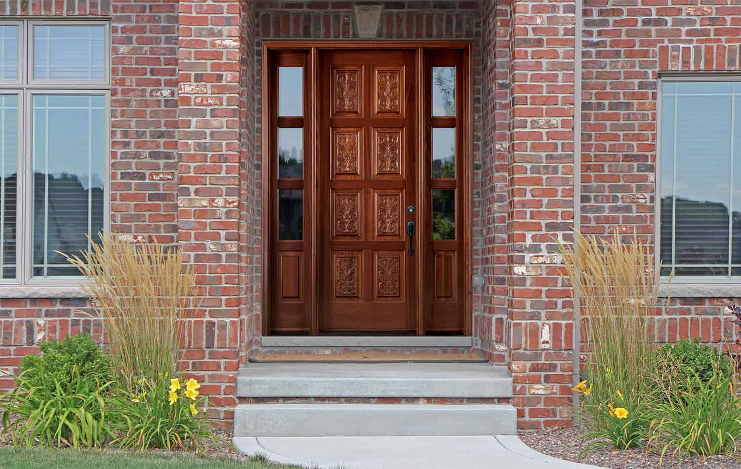 Hand-carved wood entry door on brick exterior house