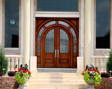 Double wood front entry door in arch shape with windows.