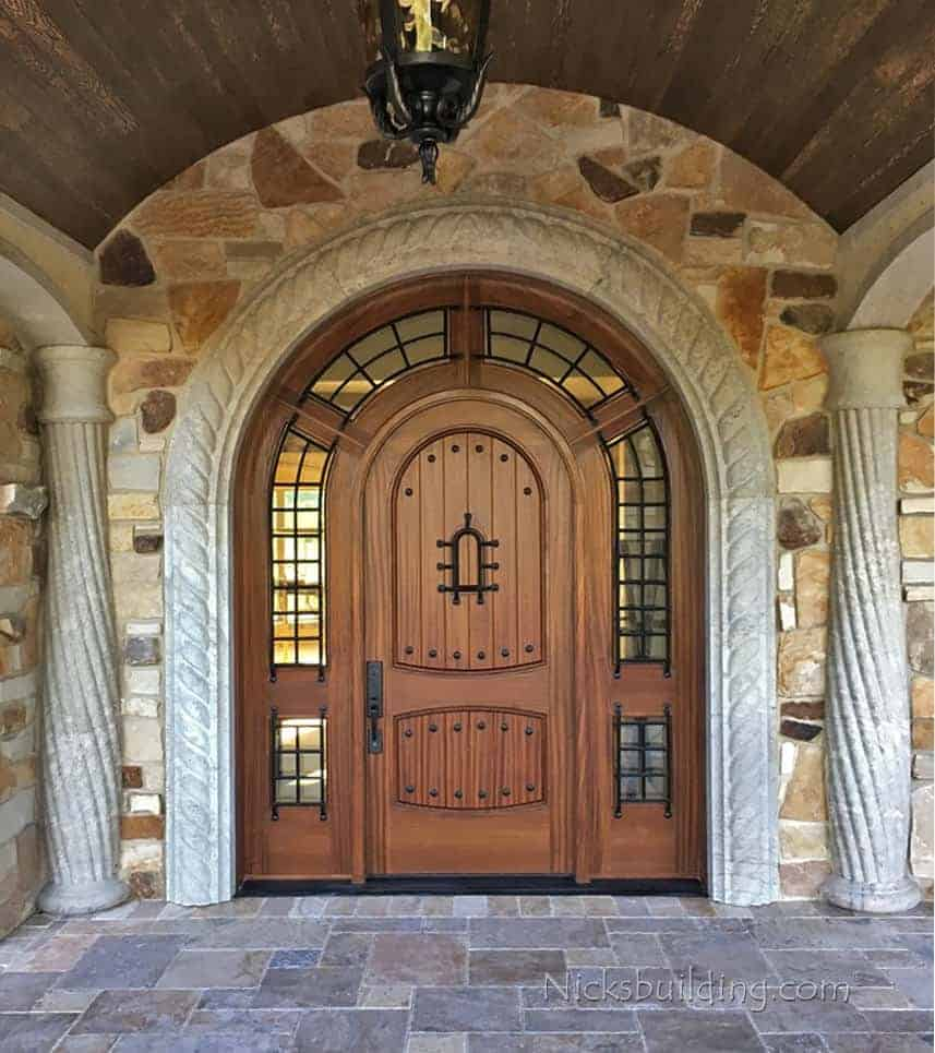Knotty alder arched front entry wood door with ornate columns on each side.