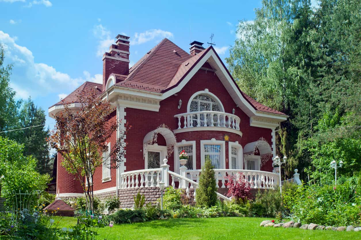 "Stunning ""gingerbread"" Victorian house with red exterior and white trim."