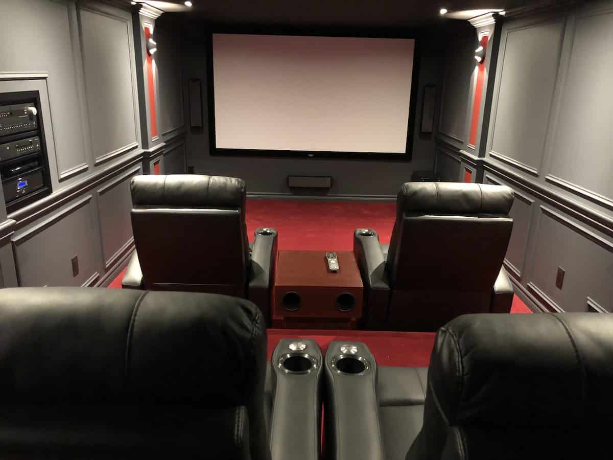 Cool small home theater built by homeowner. Includes 4 large theater seats with beverage storage, red carpet, projector screen and a sound system that will rock your world.