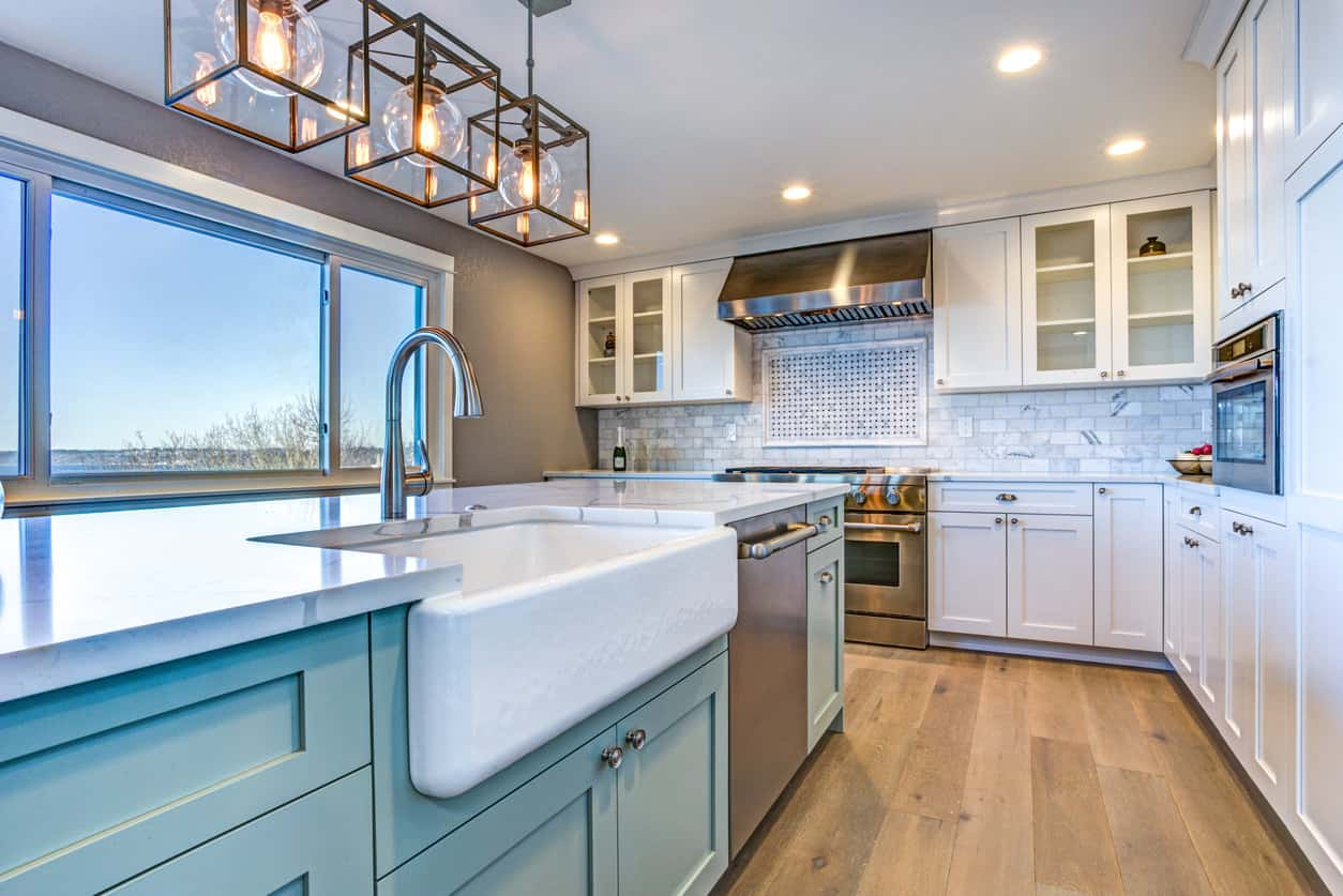 Kitchen with blue island, large white farmhouse sink, white cabinetry and wide-plank hardwood flooring all illuminated with a contemporary single unit pendant light and recessed lights.
