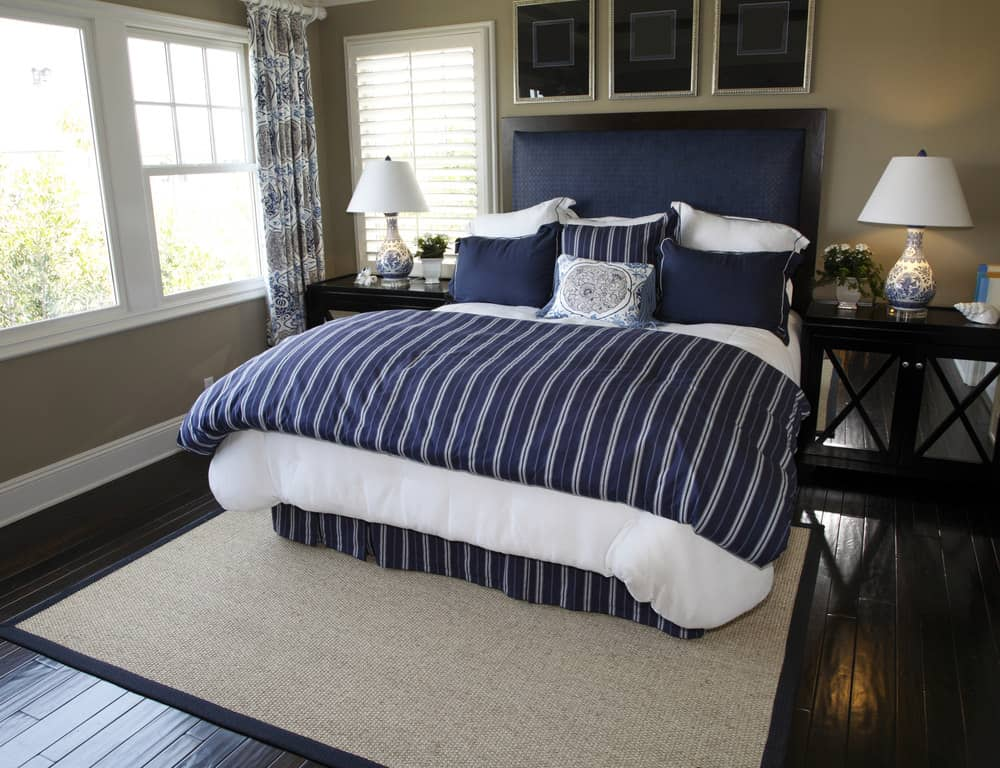 Small primary bedroom with dark wood floor, teal walls, white window trim and navy blue and white bedding.