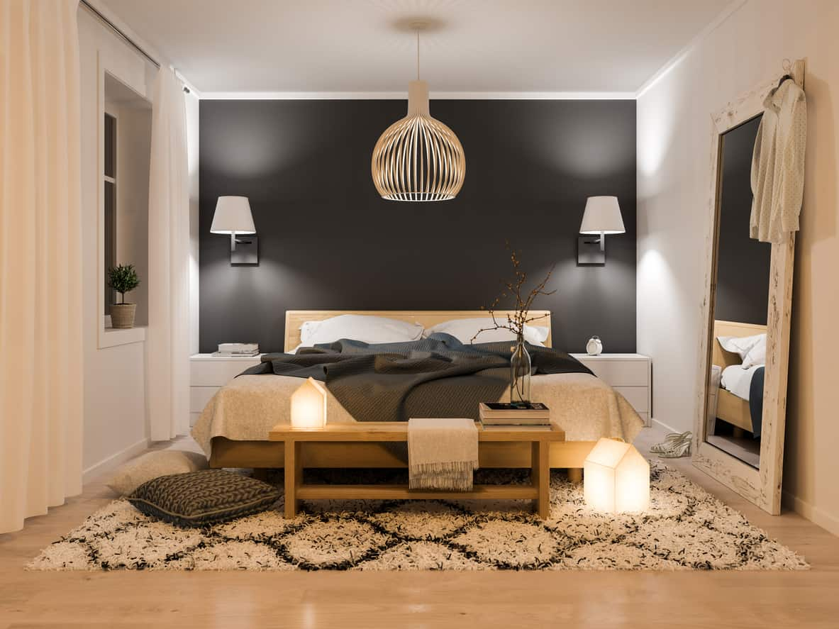 Stylish small primary bedroom with patterned area rug, wall-mounted lamps, curtains and dark accent wall.
