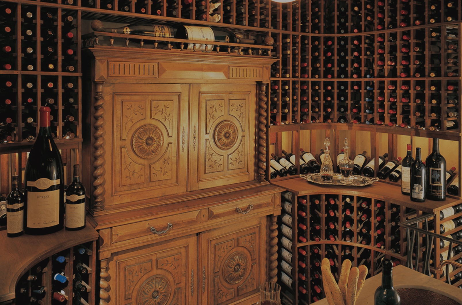 This 1,400 bottle wine cellar has custom wine storage throughout including very cool curved cabinets in the corner, overhead racking and a tasting table.