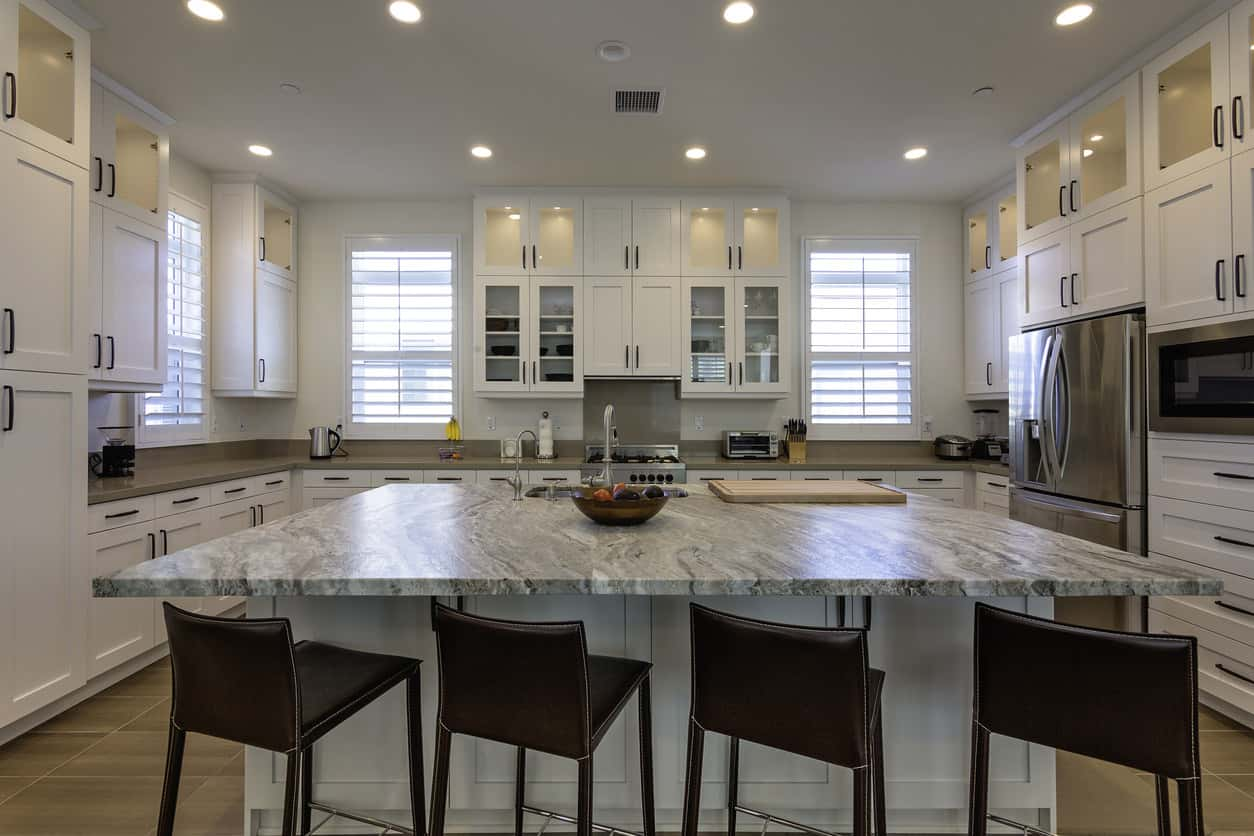 Large new U-shaped kitchen with white cabinets (a nice variety of cabinet design and layout) with a large square island in the center with an eating area for four stools.