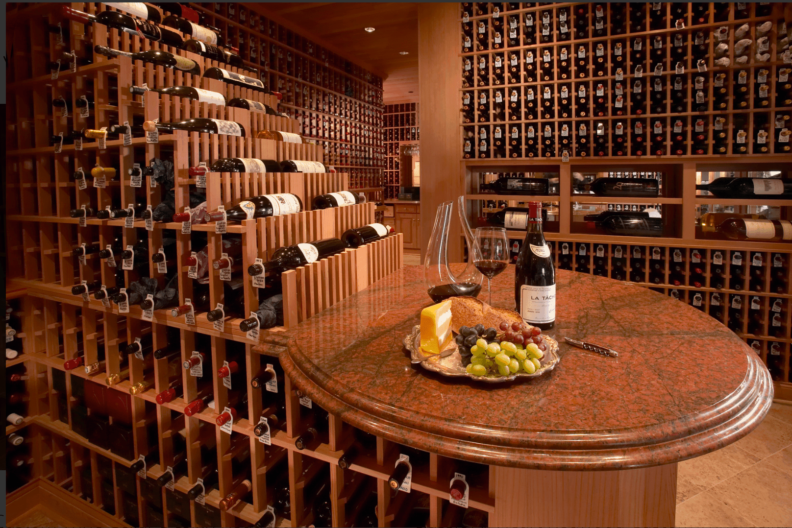 A closer look of the redwood waterfall wine storage highlighting the round marble countertop on its end.