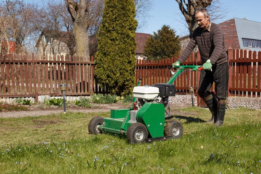 An old man uses an aerator on his lawn.