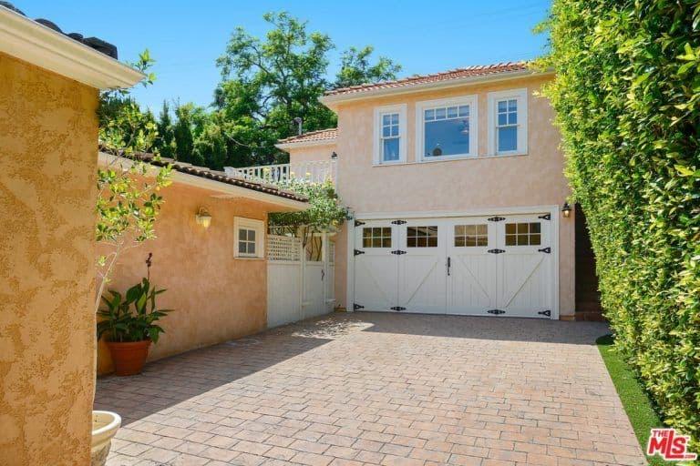 The backyard's garage features brick driveway.