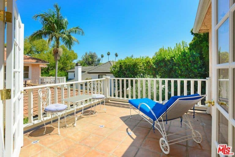 The patio on the home's balcony features a relaxing seat under the West Hollywood skies.
