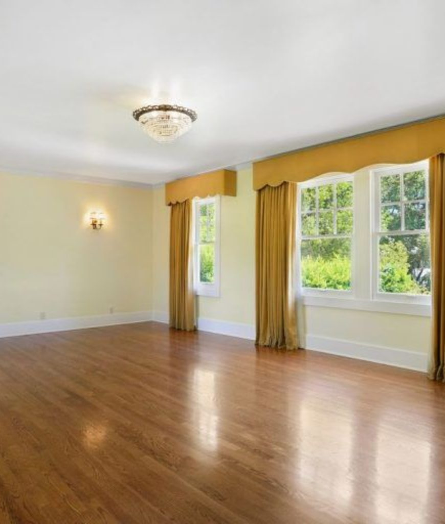 The former bedroom has french windows with classy yellow curtains along with white walls and wall lighting.