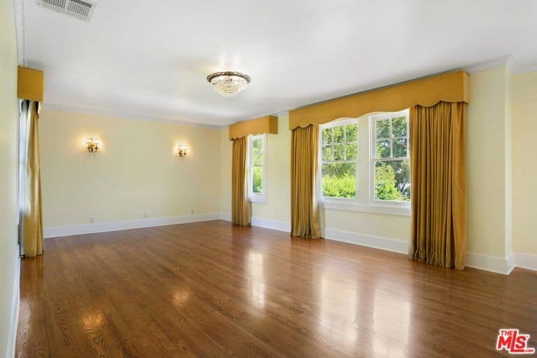 The Former Bedroom Has French Windows With Classy Yellow Curtains Along  With White Walls And Wall