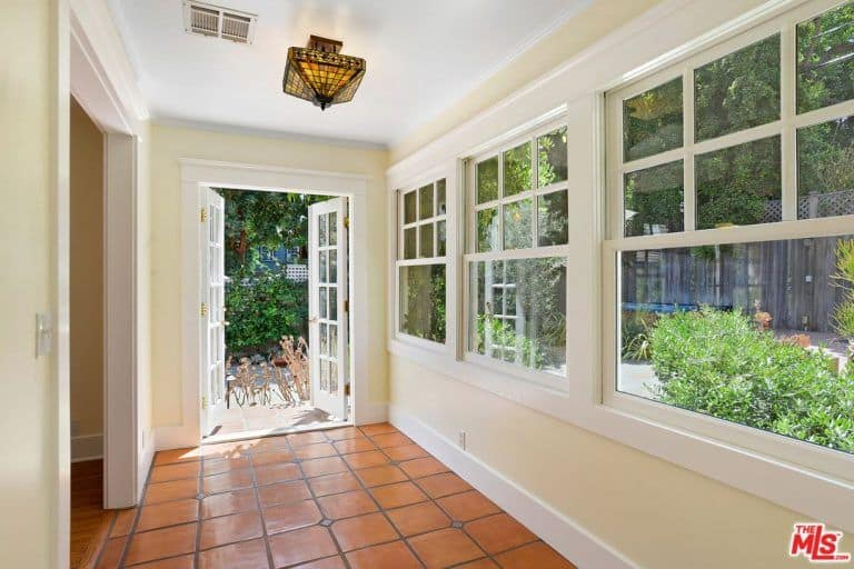 There's a hallway with white walls and french windows and door.