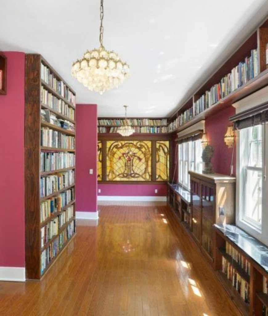 Another view of the library room featuring stylish walls and wall decor.