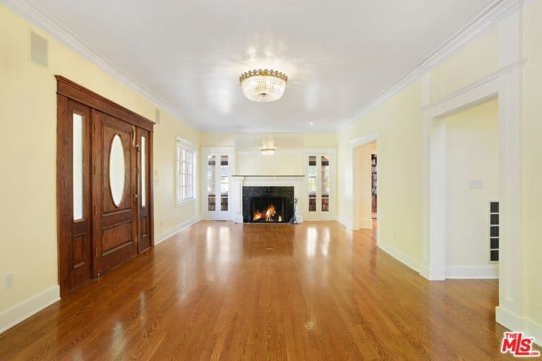The former living room features a fireplace and white walls.