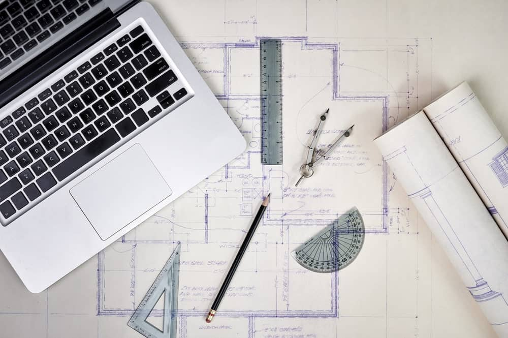 Overhead shot of architect tools including laptop, drafting measuring tools, compass, mechanical pencil, metal ruler, and tracing paper.
