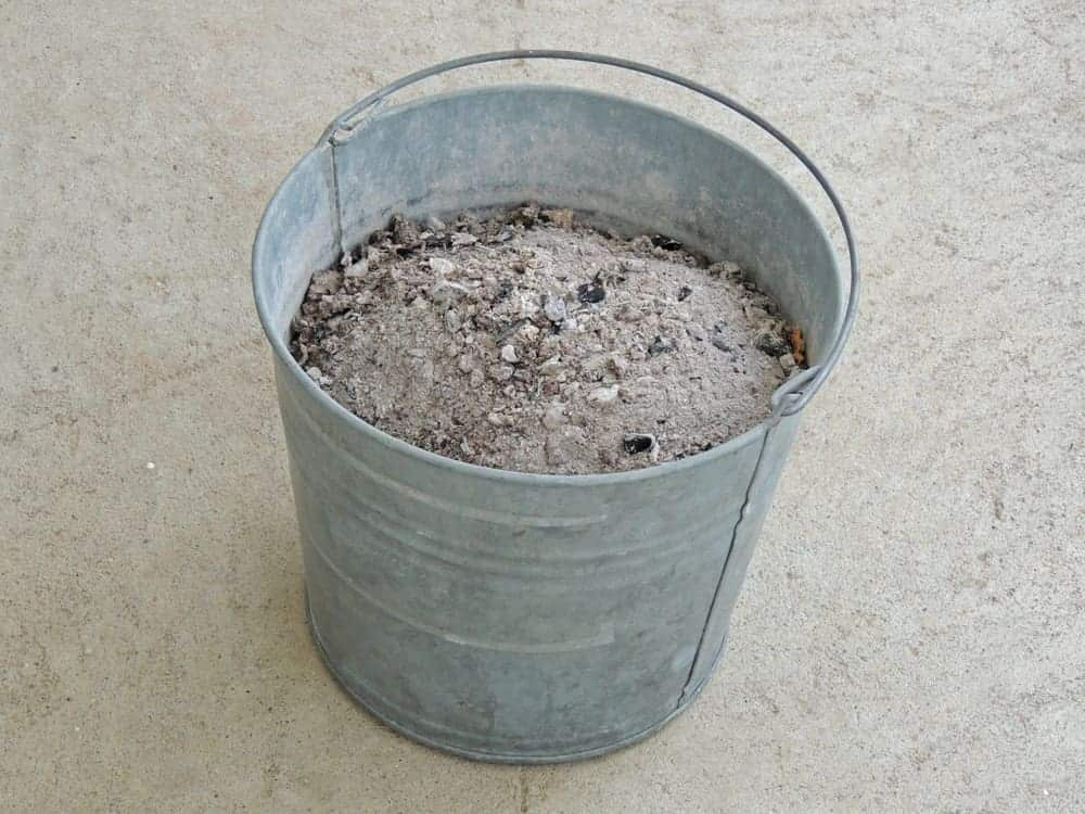 Ash bucket full of ashes on concrete background.
