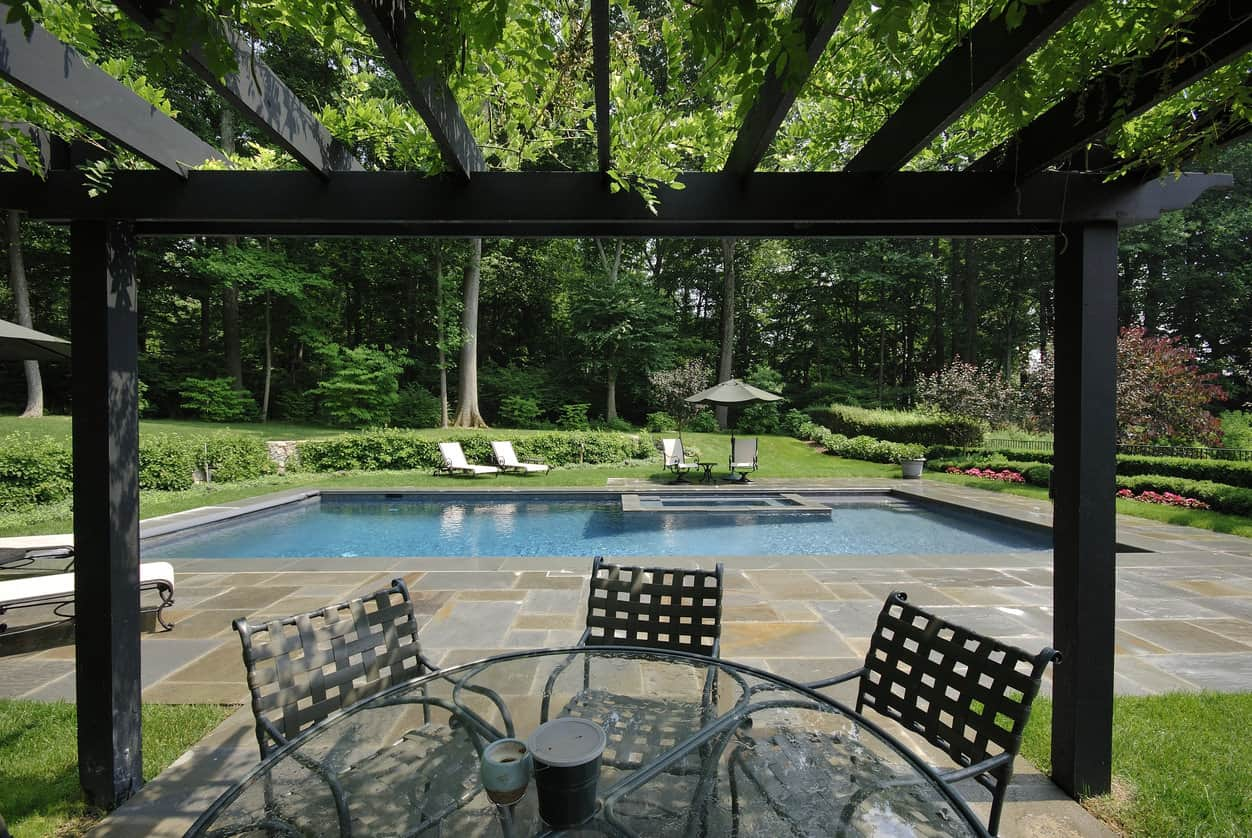 Large treed backyard with rectangle pool surrounded by a fabulous multi-colored patio.