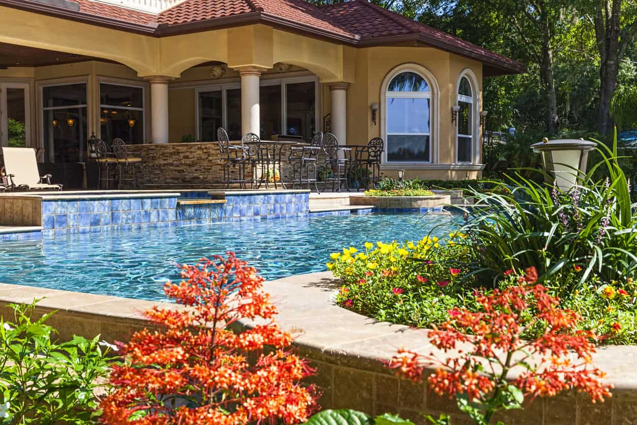 Mediterranean style home with a Mediterranean style pool. Check out the blue tile made to look like a cascading waterfall into this beautiful rectangle pool surrounded by colorful gardens.
