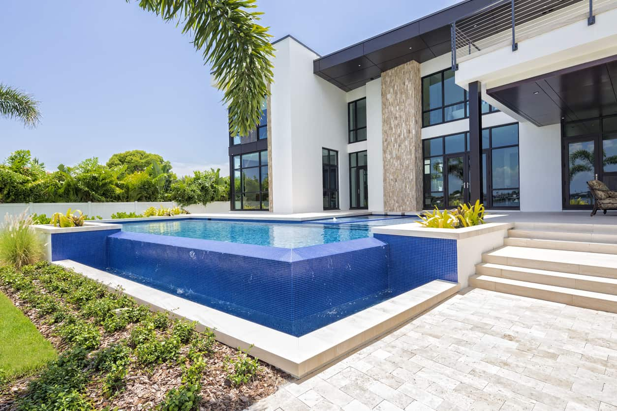 Here's a side view of an infinity pool that uses the exterior infinity edge as a way to enhance the backyard by making it a fountain waterfall. This is a very clever pool design.