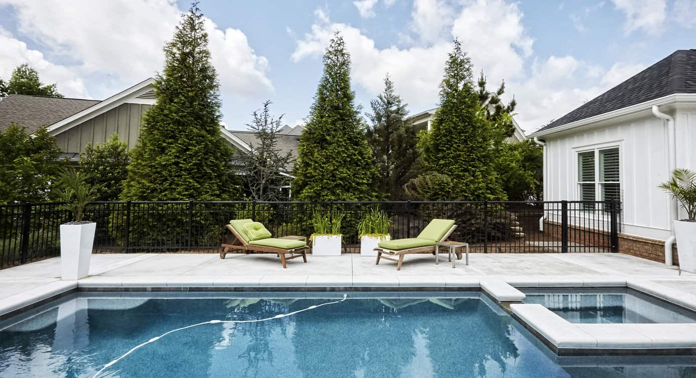 Another example of a great inground pool in a small backyard. In fact, that's a fairly small pool with embedded attached hot tub. Notice how striking the white tile patio is. Something to keep in mind.