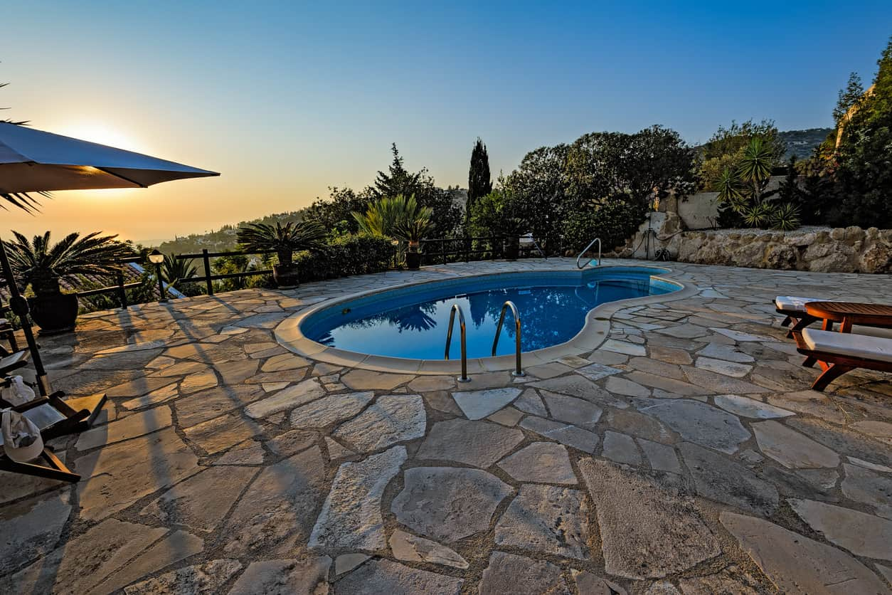 Example of a small pool on cliffside property with a massive flagstone patio that takes up the entire backyard.