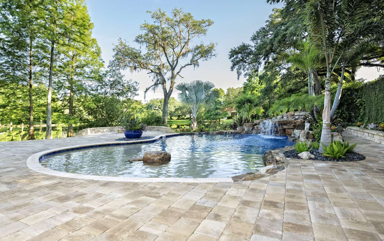 Zero-entry pool with waterfall in large heavily treed backyard with huge surrounding patio.